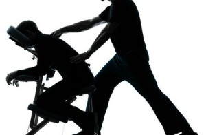two men performing chair back massage in silhouette studio on white background